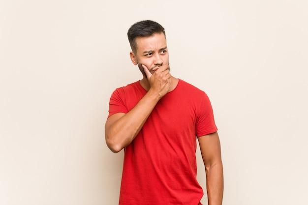 Młody południowo-azjatycki człowiek zamyślony, patrząc na kopię miejsca obejmujące usta ręką.