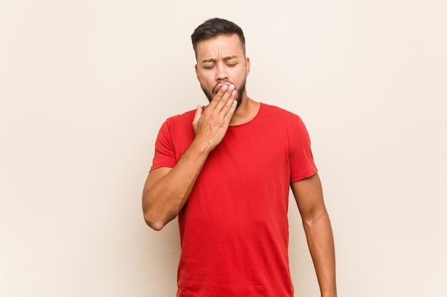 Młody południowo-azjatycki człowiek ziewanie pokazując zmęczony gest obejmujący usta ręką.