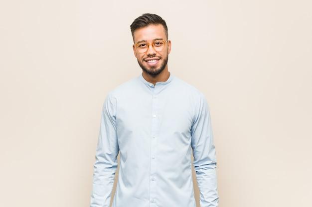 Młody południowoazjatycki biznesmen szczęśliwy, uśmiechnięty i wesoły