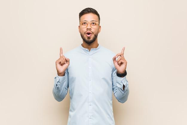 Młody południowoazjatycki biznesowy mężczyzna wskazuje do góry nogami z rozpieczętowanym usta.