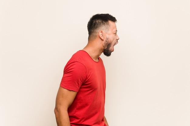 Młody południowoazjatycki mężczyzna krzyczy w kierunku kopii przestrzeni
