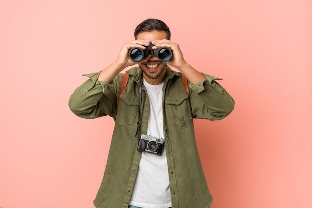Młody południowoazjatycki mężczyzna patrzeje przez lornetki.