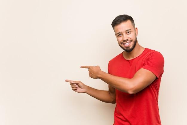 Młody południowoazjatycki mężczyzna podekscytowany wskazuje palcami wskazującymi.