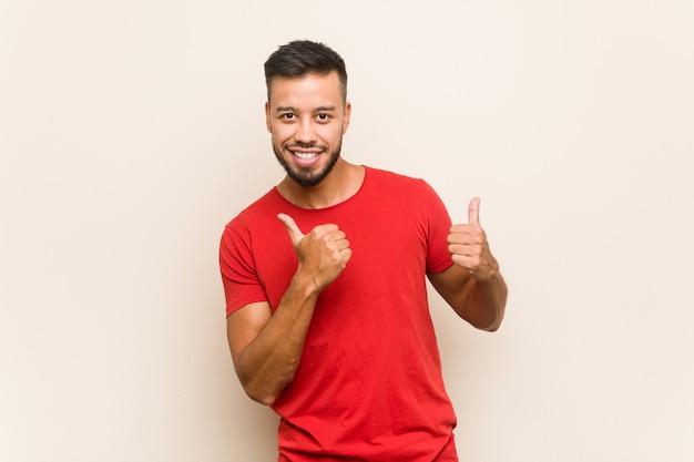 Młody południowoazjatycki mężczyzna podnosi kciuki do góry, uśmiecha się i pewny siebie.
