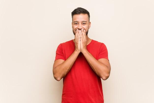 Młody południowoazjatycki mężczyzna śmiejący się z czegoś, zakrywający usta dłońmi.