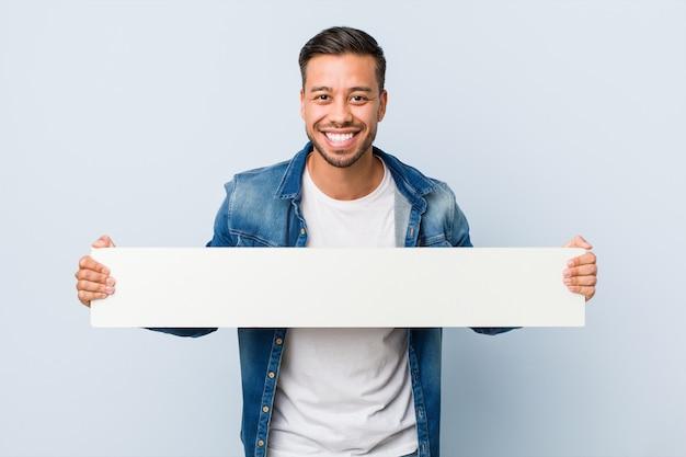 Młody południowoazjatycki mężczyzna trzyma białego plakat.