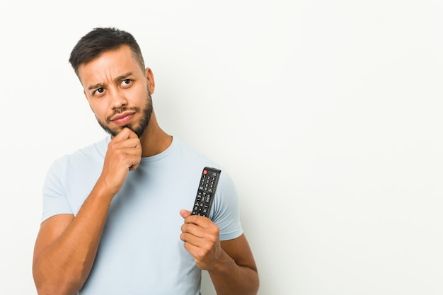 Młody południowoazjatycki mężczyzna trzyma kontroler telewizyjny, patrzy w bok z powątpiewającym i sceptycznym wyrazem twarzy.