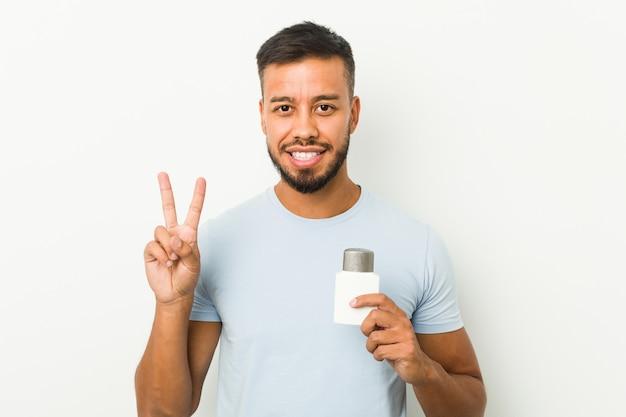 Młody południowoazjatycki mężczyzna trzyma po goleniu krem pokazujący numer dwa palcami.