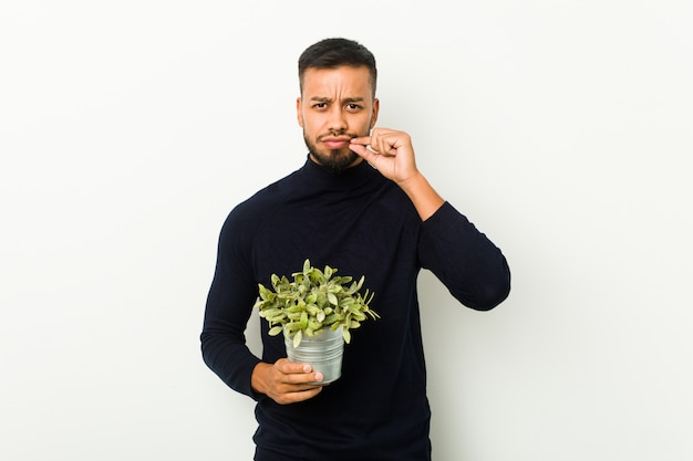 Młody południowoazjatycki mężczyzna trzyma rośliny z palcami na ustach, utrzymując sekret.