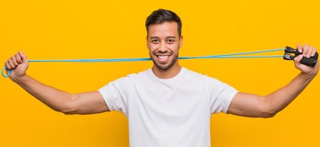 Młody południowoazjatycki mężczyzna trzyma skakankę.