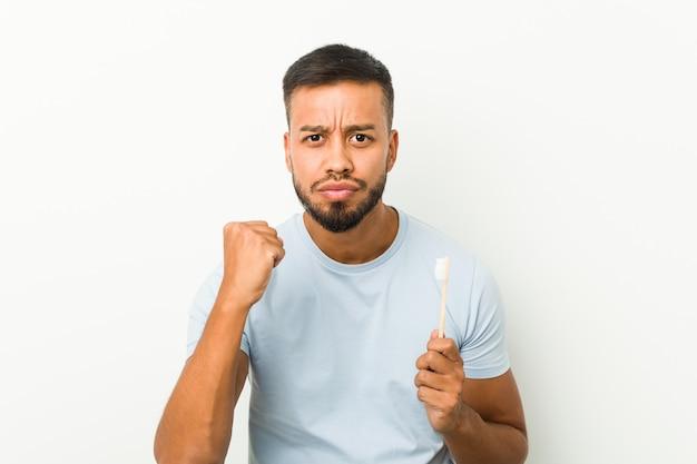 Młody południowoazjatycki mężczyzna trzyma szczoteczkę do zębów, pokazując pięść do kamery, agresywny wyraz twarzy.