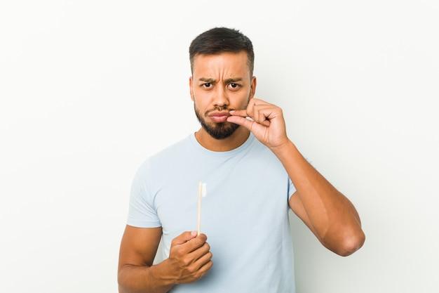 Młody południowoazjatycki mężczyzna trzyma szczoteczkę do zębów z palcami na ustach, zachowując tajemnicę.