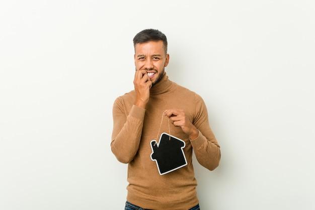 Młody południowoazjatycki mężczyzna trzyma w domu ikonę obgryzającą paznokcie, nerwowy i bardzo niespokojny.