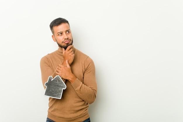 Młody południowoazjatycki mężczyzna trzymający ikonę domu, patrzył w bok z wyrazem wątpliwości i sceptycyzmu.