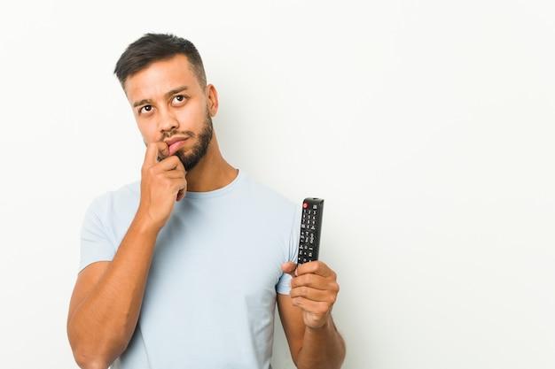 Młody południowoazjatycki mężczyzna trzymający kontroler tv zrelaksował się myśląc o czymś, patrząc na odbitkową przestrzeń.
