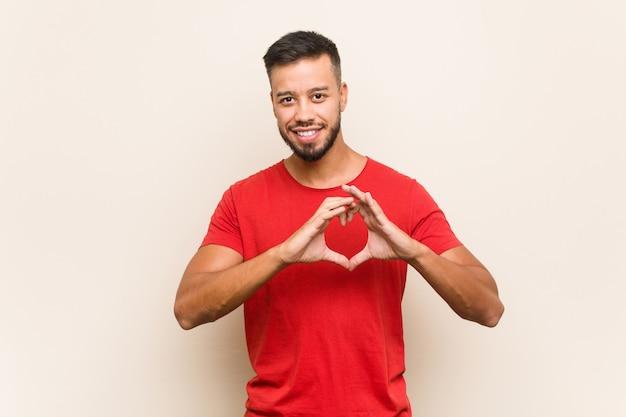 Młody południowoazjatycki mężczyzna uśmiecha się kształt serca z rękami i pokazuje.