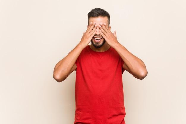 Młody południowoazjatycki mężczyzna zakrywa oczy dłońmi, uśmiecha się szeroko, czekając na niespodziankę.