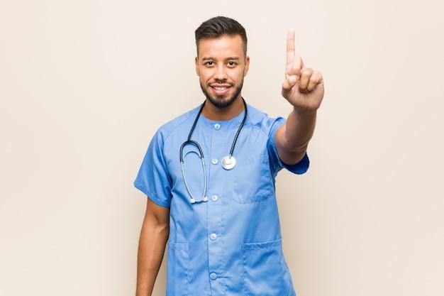 Młody południowoazjatycki pielęgniarka mężczyzna pokazuje liczbę jeden z palcem.
