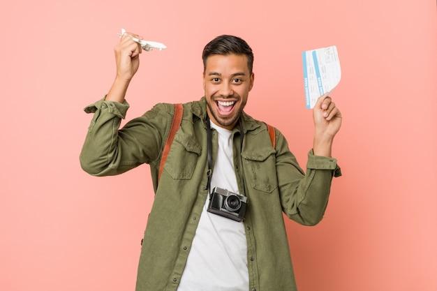 Młody południowoazjatycki podróżnik posiadający bilety lotnicze.