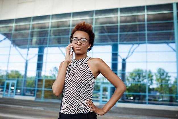 Młody pomyślny afrykański bizneswoman mówi na telefonie nad centrum biznesu.