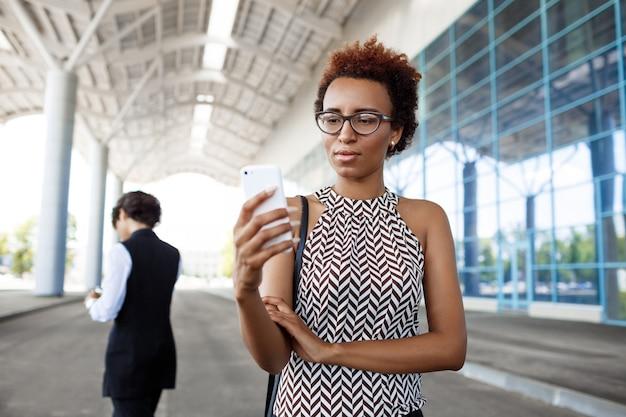 Młody pomyślny afrykański bizneswoman patrzeje telefon nad centrum biznesu.