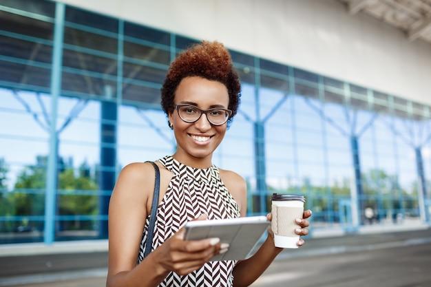 Młody pomyślny afrykański bizneswoman stoi blisko centrum biznesu w szkłach.