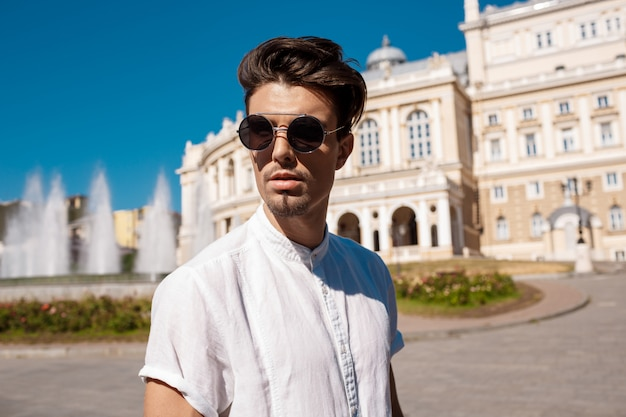 Młody pomyślny biznesmen chodzi wokoło słonecznego miasta w okularach przeciwsłonecznych.