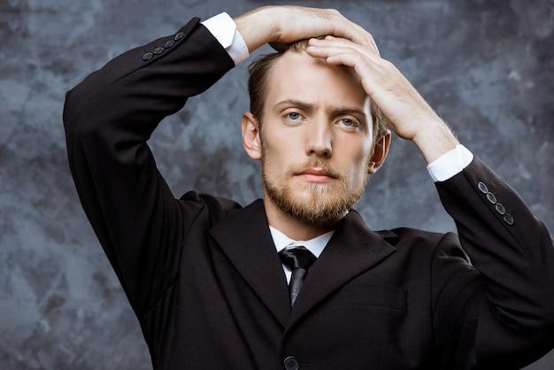 Młody pomyślny biznesmen koryguje włosy