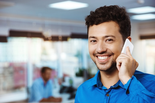 Młody pomyślny biznesmen mówi na telefonie, ono uśmiecha się, nad biurem