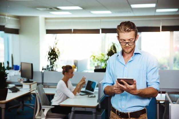 Młody pomyślny biznesmen ono uśmiecha się, patrzejący pastylkę, nad biurem