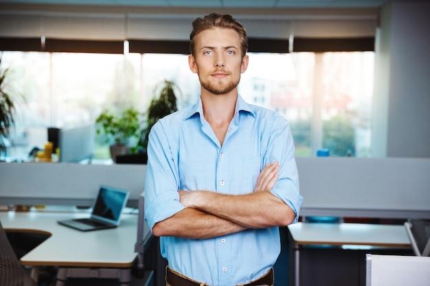 Młody pomyślny biznesmen ono uśmiecha się, pozuje z krzyżować rękami, nad biurem