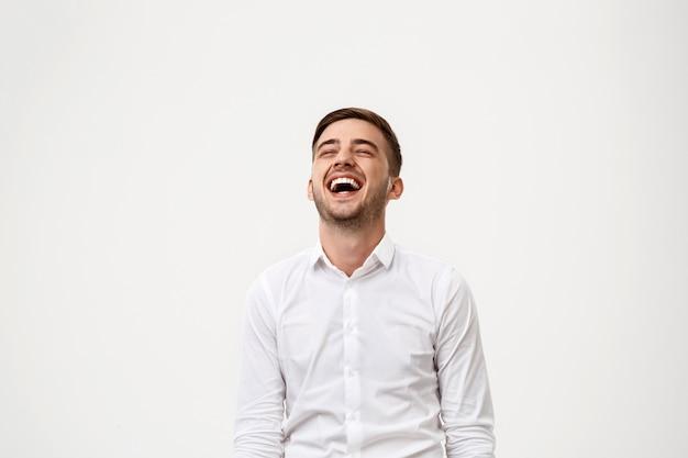 Młody pomyślny biznesmen ono uśmiecha się, śmia się.