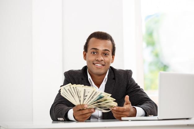 Młody pomyślny biznesmen ono uśmiecha się, trzymający pieniądze, siedzi przy miejscem pracy