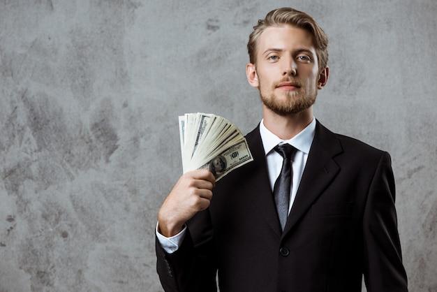 Młody pomyślny biznesmen w kostiumu mienia pieniądze