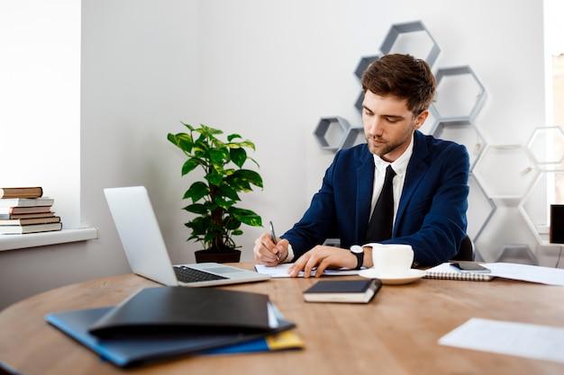 Młody pomyślny biznesmena obsiadanie przy miejscem pracy, biurowy tło.