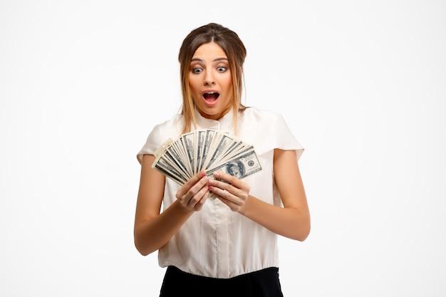 Młody pomyślny bizneswoman trzyma pieniądze nad białym tłem.
