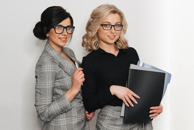 Młody pomyślny bizneswoman w szkłach z dokumentów ono uśmiecha się