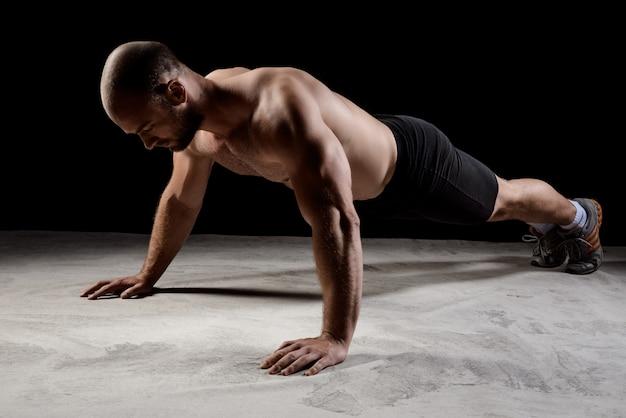 Młody potężny sportowiec trening pompek na ciemnej ścianie.