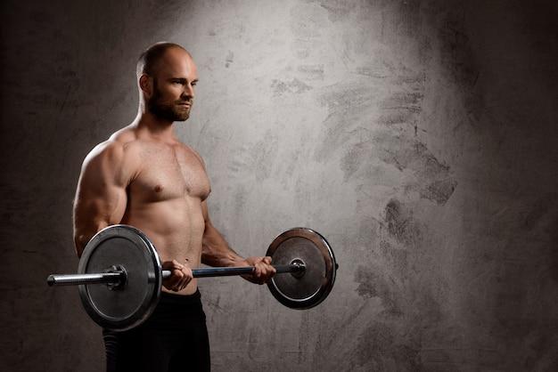 Młody potężny sportowiec trenujący ze sztangą na ciemnej ścianie.