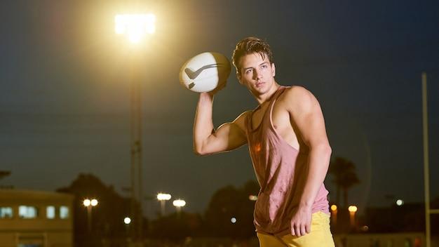 Młody potu futbolu amerykańskiego gracz pozuje z piłką na stadium