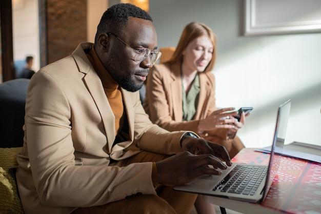 Młody poważny afrykanin patrzący na ekran laptopa podczas pisania