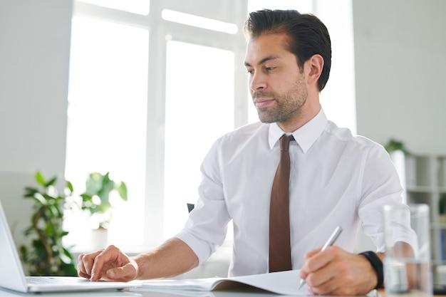Młody poważny analityk lub ekspert finansowy przeglądający dane online na ekranie laptopa