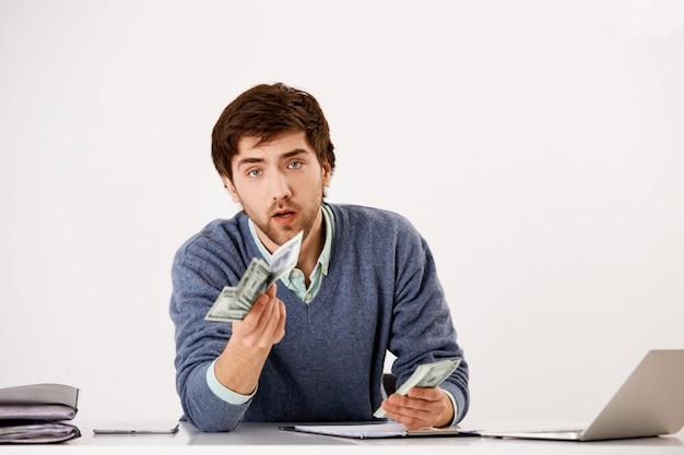Młody poważny biznesmen, licząc pieniądze siedzi biurko z laptopem, przedłuża dolary, daje połowę gotówki partnerowi biznesowemu, czyniąc transakcję