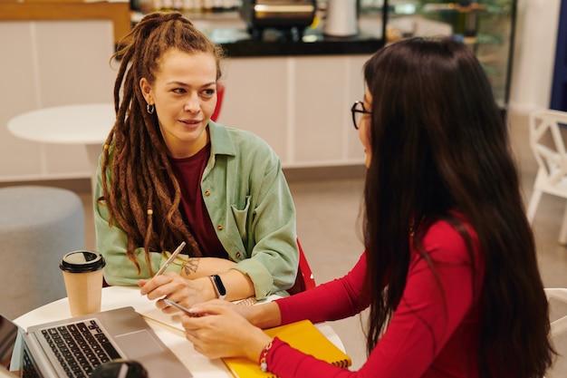 Młody poważny biznesmen patrzący na swojego kolegi z rasy mieszanej podczas omawiania punktów pracy na spotkaniu w biurze typu open space