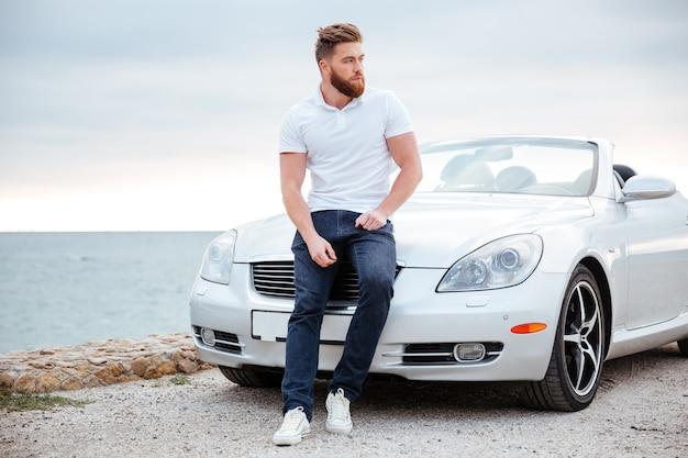 Młody poważny brodaty mężczyzna wsparty na swoim samochodzie zaparkowanym na plaży