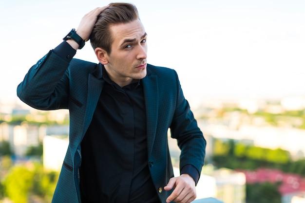 Młody poważny busunessman w ciemnym garniturze, zegarku i czarnej koszuli stoi na dachu