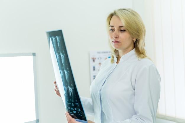 Młody poważny kompetentny lekarz kobiet patrząc na zdjęcie rentgenowskie w gabinecie lekarskim.