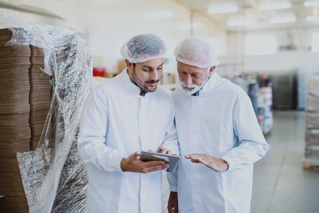 Młody poważny menedżer w sterylnym mundurze za pomocą tabletu do sprawdzania towarów i rozmowy z pracownikiem. wnętrze fabryki żywności.