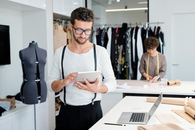 Młody, poważny męski krawiec z tabletem przegląda kreatywne pomysły online podczas pracy nad nową kolekcją mody