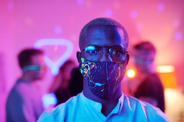 Młody poważny mężczyzna o afrykańskim pochodzeniu etnicznym w okularach i masce ochronnej, patrzący na ciebie, stojący naprzeciw swoich przyjaciół cieszących się domową imprezą